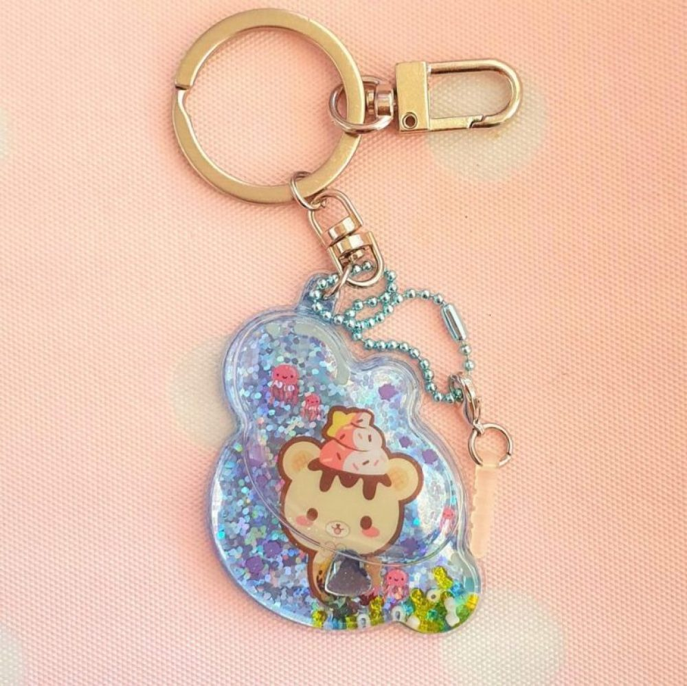 Buy this super adorable cute liquid keychain charm featuring Yummiibear as a mermaid! Filled with glitter pieces.